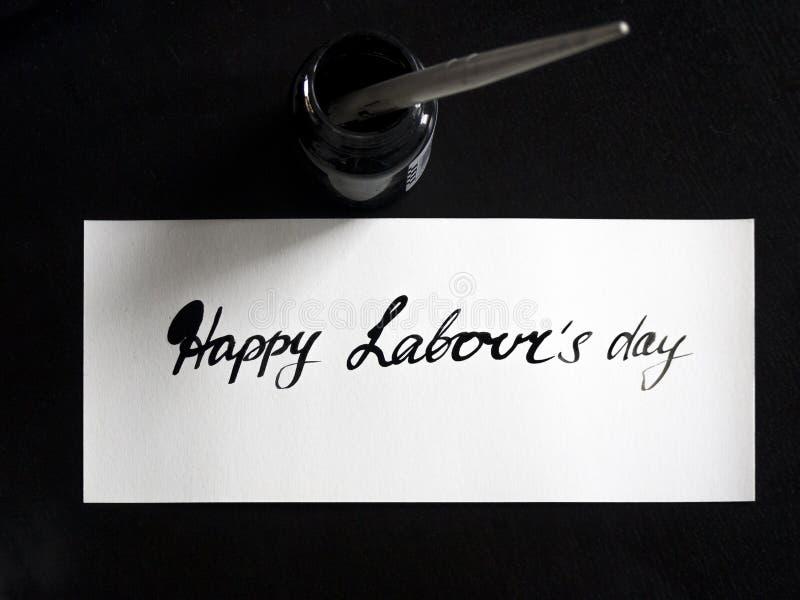 Glückliche Arbeits-` s Tageskalligraphie und lattering Postkarte Draufsicht mit calligraph im Tintenbehälter stockbild