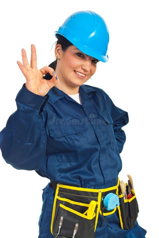 Glückliche Arbeitskraftfrau, die o.k. darstellt stockfotografie