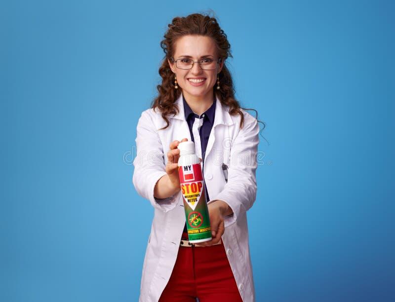 Glückliche Arztfrau, die Insektenvertilgungsmittel auf Blau zeigt stockfotos