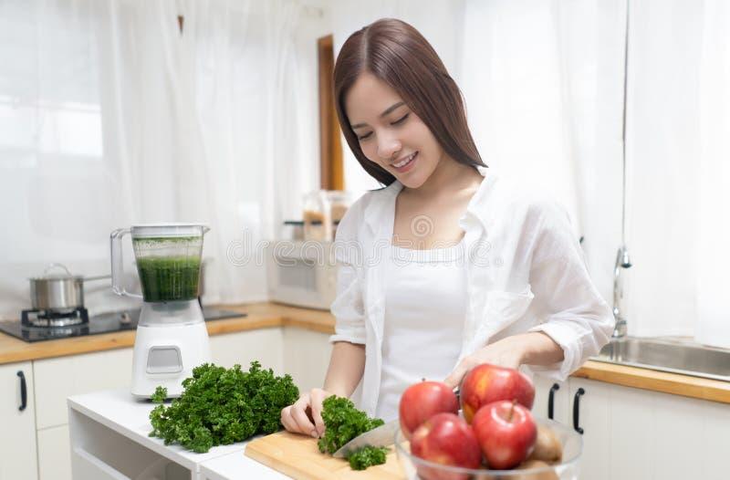 Glückliche Asiatin, die gesundes grünes Gemüse in der Mischmaschine in ihrer unbedeutenden Küche vorbereitet Vegetarisches, gesun lizenzfreies stockbild