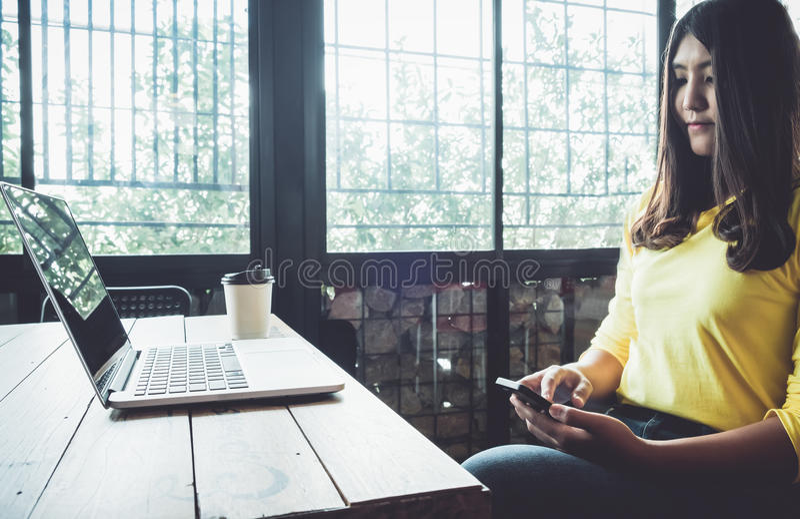 Glückliche Asiatin, die an ihrem Handy plaudert, bei der Entspannung im Café während der Freizeit, stockfotografie