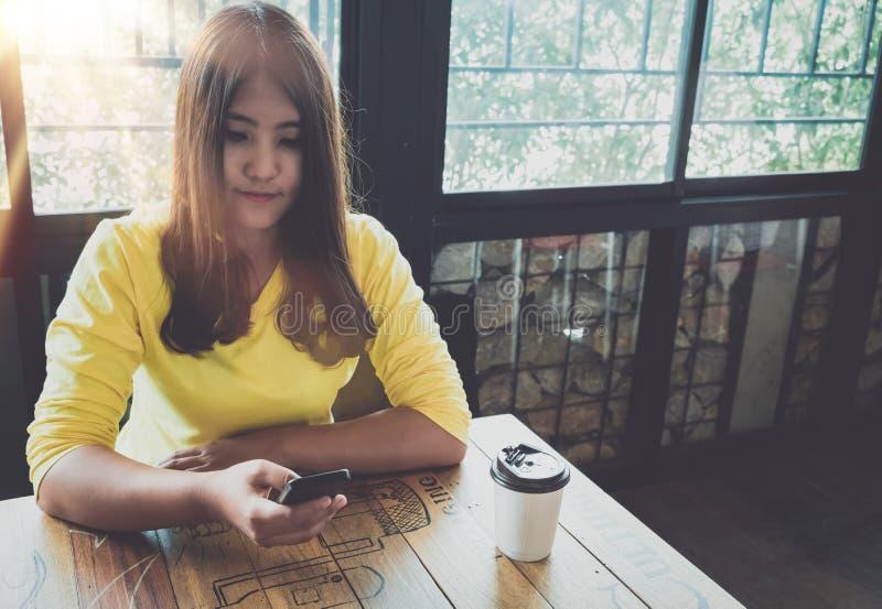 Glückliche Asiatin, die an ihrem Handy plaudert, bei der Entspannung im Café während der Freizeit, stockbild