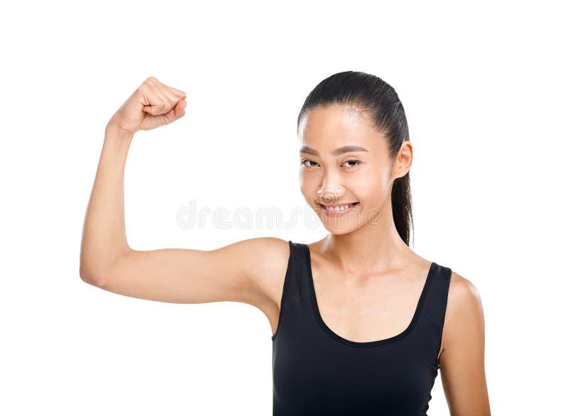 Glückliche Asiatin, die Muskeln auf den Handbizepsen lokalisiert zeigt stockfotografie