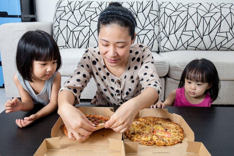 Glückliche asiatische chinesische Familie, die zusammen Pizza genießt lizenzfreie stockbilder
