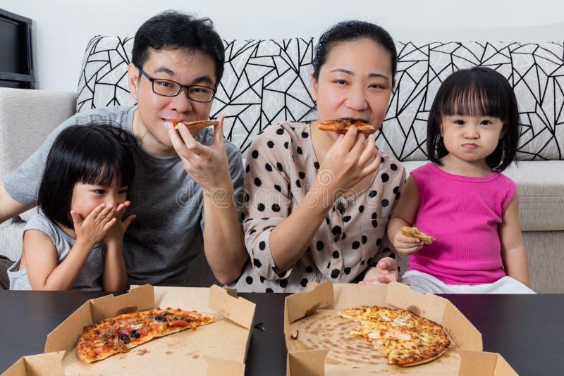 Glückliche asiatische chinesische Familie, die zusammen Pizza isst stockbild