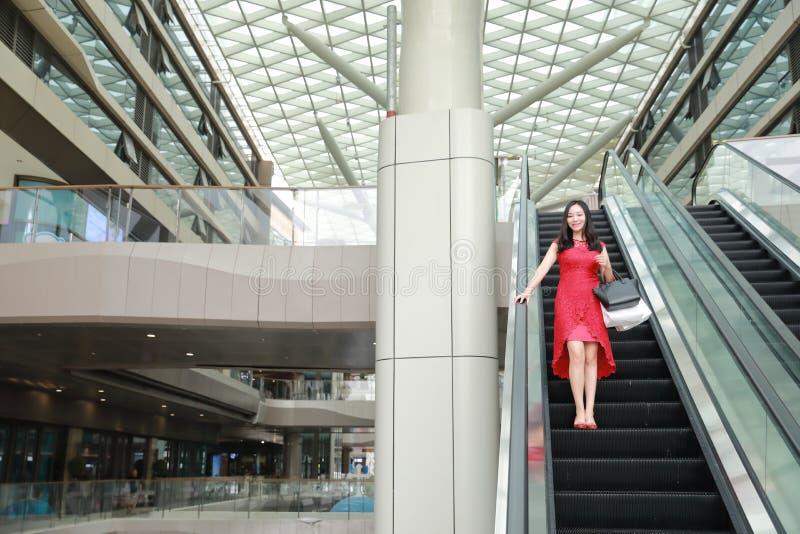 Glückliche asiatische chinesische moderne Einkaufstaschen der modernen Frau in einem Käuferlächelnlachen-Aufzugsaufzug der Mallsp stockfoto