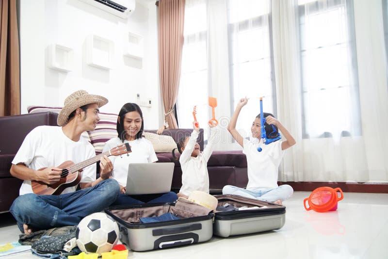 Glückliche asiatische Familie auf einem Boden zu Hause, der Urlaubsreisereise plant stockbilder