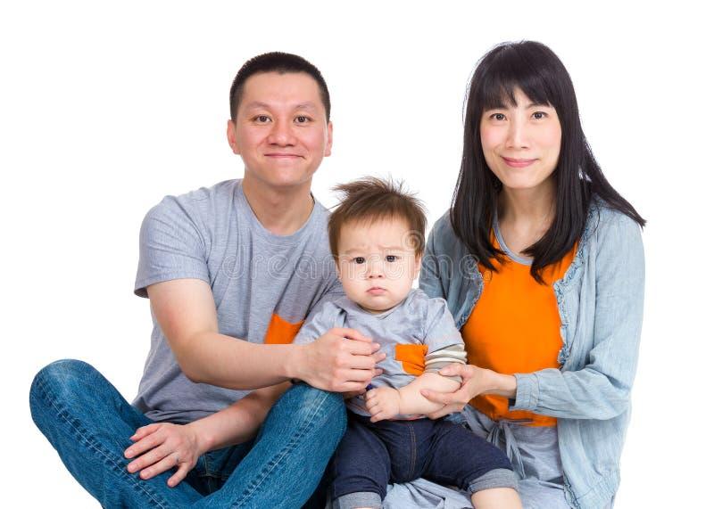 Glückliche asiatische Familie, die auf Boden sitzt lizenzfreies stockbild
