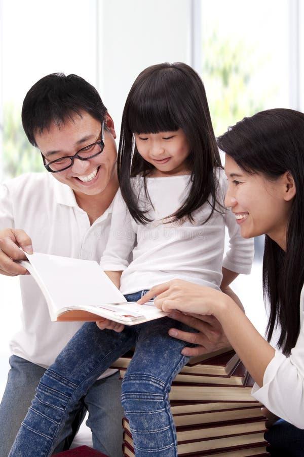 Glückliche asiatische Familie, die zusammen studiert lizenzfreie stockbilder