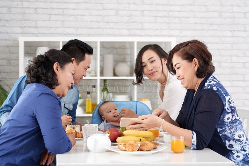 Glückliche asiatische Familie am Frühstückstische lizenzfreies stockbild