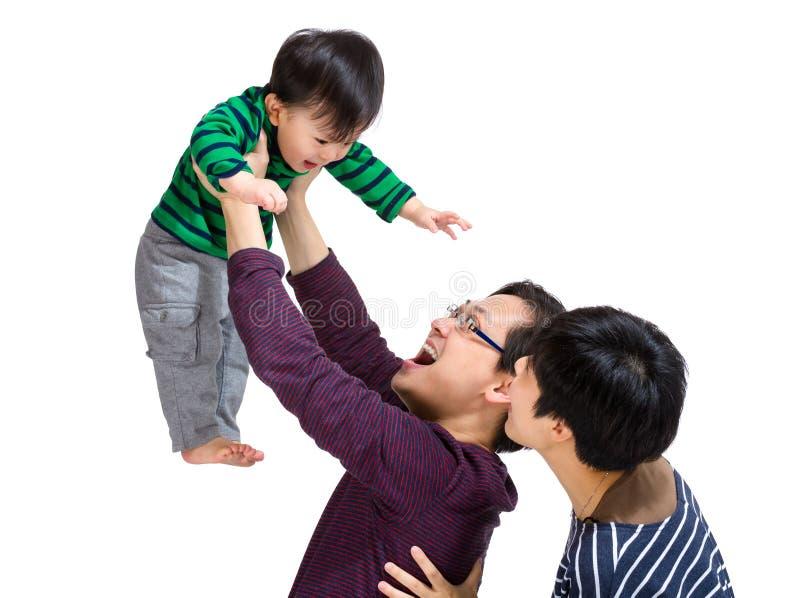 Glückliche asiatische Familie mit dem Vati, der oben wirft stockfotos