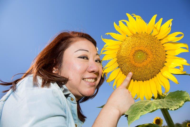 Glückliche asiatische Frau auf dem Sonnenblumenblumengebiet lizenzfreies stockfoto