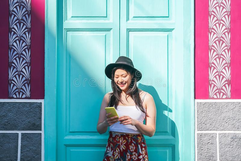 Glückliche asiatische Frau, die das intelligente Mobiltelefon im Freien - chinesisches Modemädchen aufpasst auf neue Tendenzsozia lizenzfreies stockbild