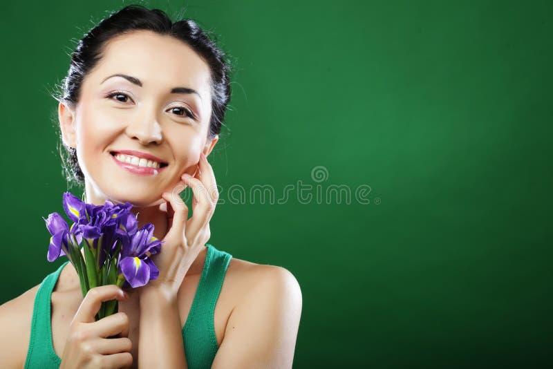 Glückliche asiatische Frau, die einen Blumenstrauß von Iris hält stockfotos