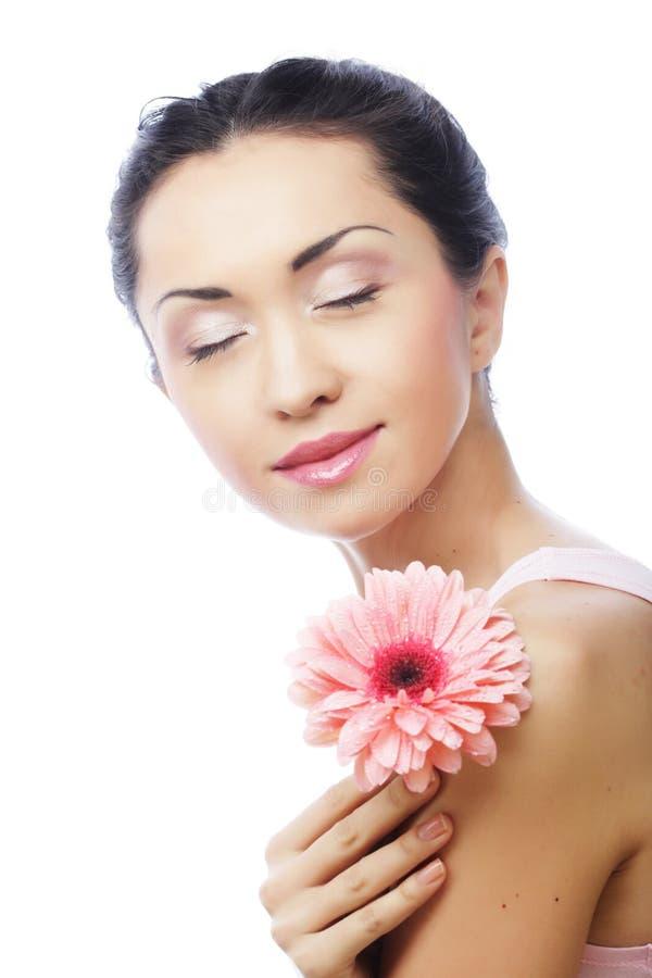 Glückliche asiatische Frau, die einen rosa Gerbera hält stockbild