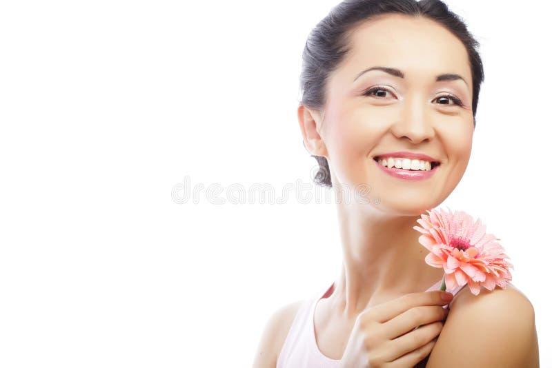 Glückliche asiatische Frau, die einen rosa Gerbera hält lizenzfreie stockbilder