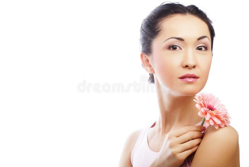 Glückliche asiatische Frau, die einen rosa Gerbera hält stockfotografie