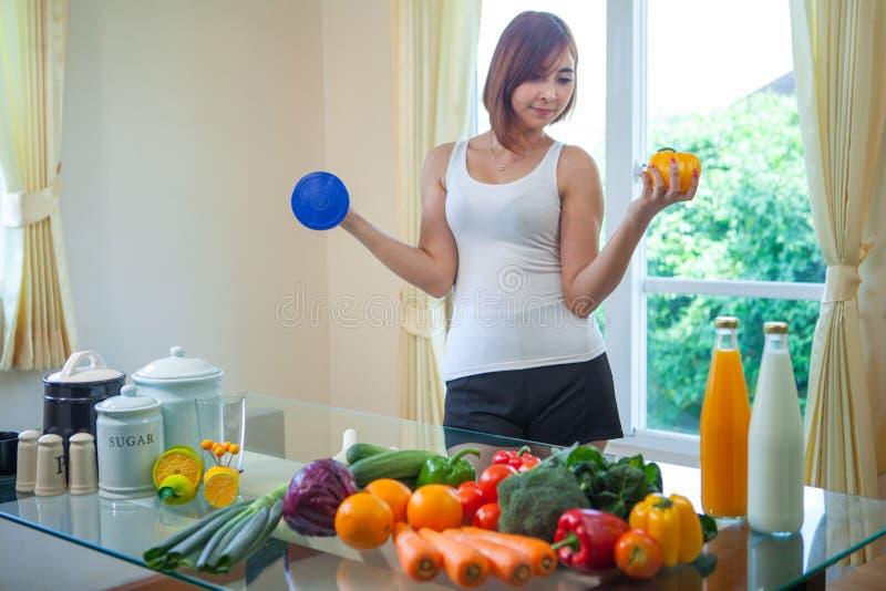 Glückliche asiatische Frau, die grünen Salat des Gemüses kocht lizenzfreie stockfotos