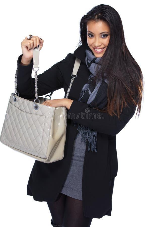 Glückliche asiatische Frau, die nach etwas in ihrem Beutel sucht lizenzfreies stockbild