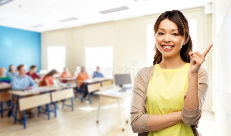 Glückliche asiatische Frau, die oben Finger in der Schule zeigt lizenzfreies stockbild