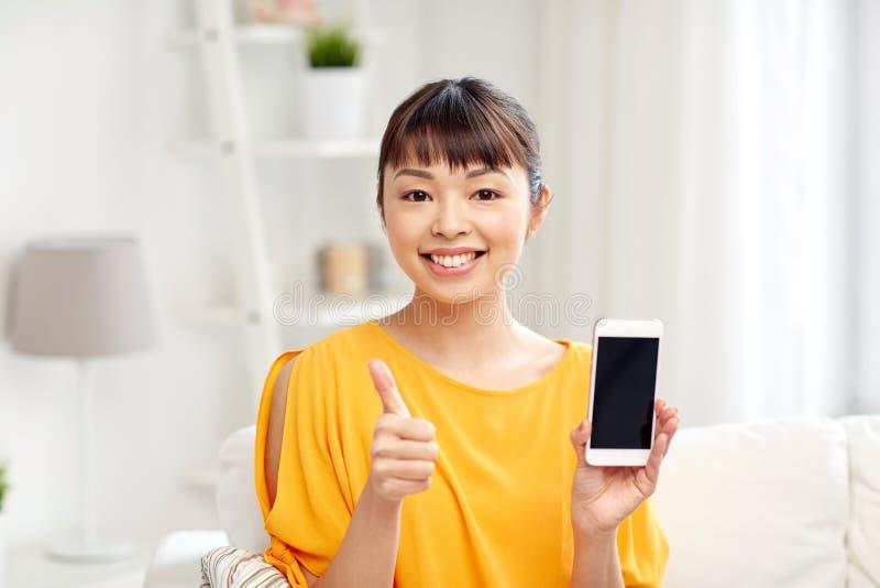 Glückliche asiatische Frau, die zu Hause Smartphone zeigt lizenzfreie stockfotos