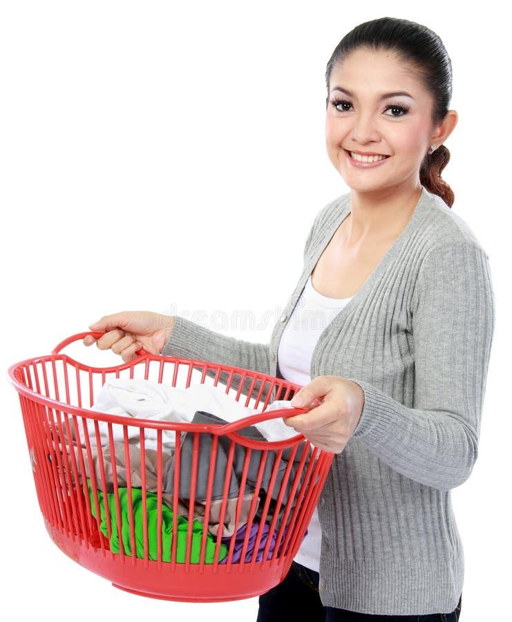 Glückliche asiatische Frau mit einem Korb von loundry lizenzfreie stockfotografie