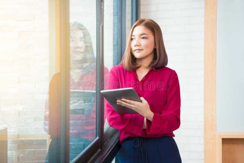 Glückliche asiatische Geschäftsfrau, die das große Fenster hält sie bereitsteht stockfotografie