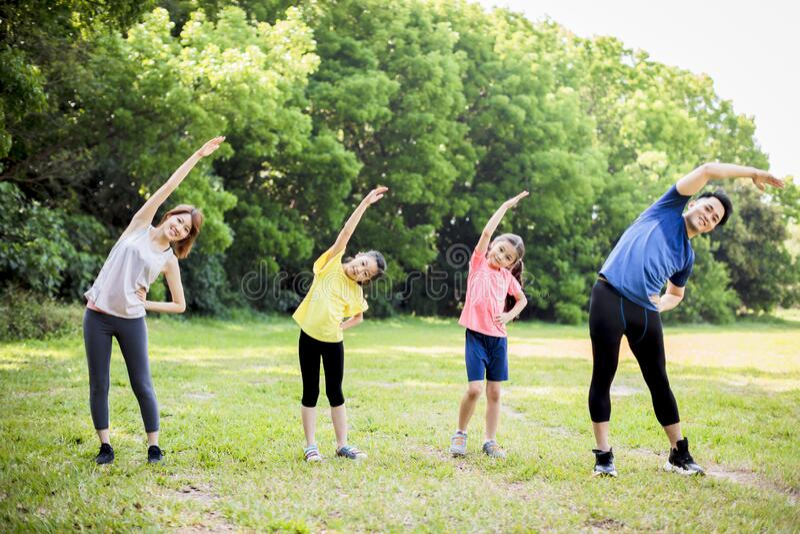 Glückliche asiatische junge Familie, die gemeinsam im Park trainiert stockfoto