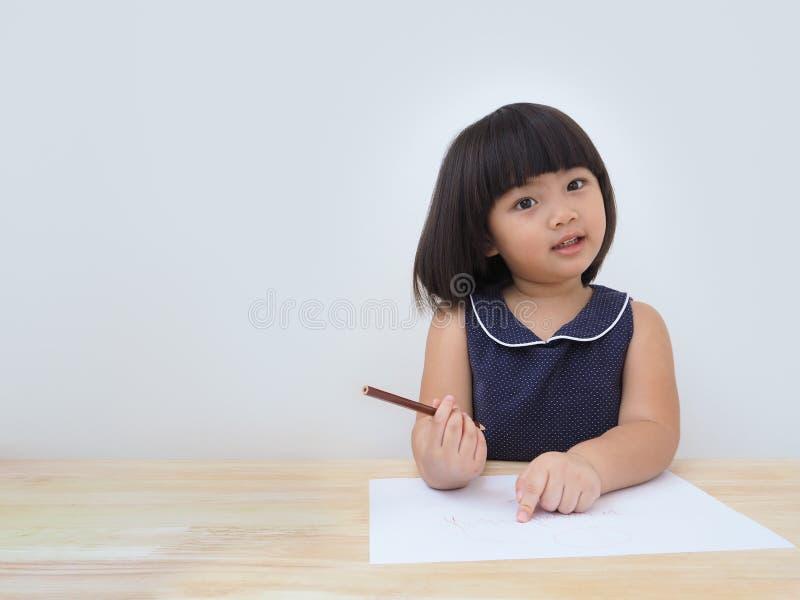 Glückliche asiatische Kindermädchenzeichnung mit farbigem Bleistift, Kind, das zu Hause lernt und spielt stockbilder