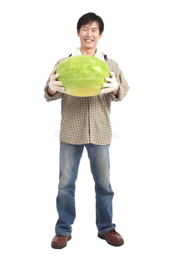 Glückliche asiatische Landwirtholdingwassermelone stockfotografie