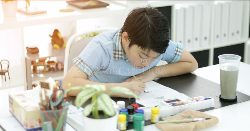 Glückliche asiatische nette Kindermalerei-Wasserfarbe auf Papier stockfoto