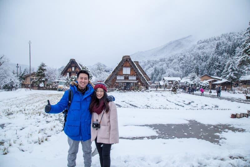 Glückliche asiatische Paare mit herein schneien Shirakawa-gehen stockfotos