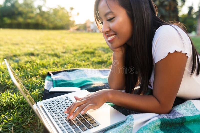 Glückliche asiatische Studentin, die auf ein Gras am Campus legt stockbild