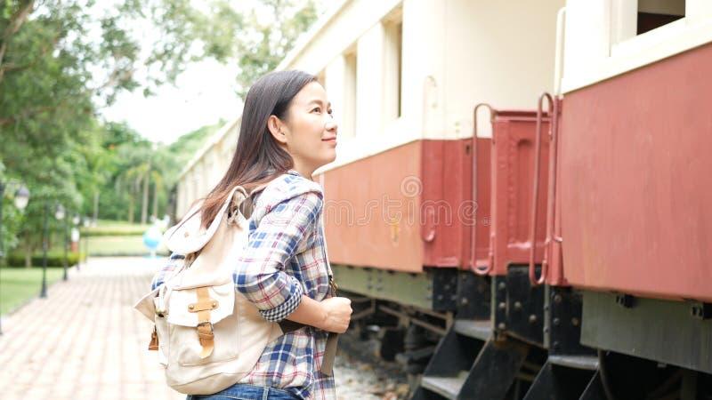Glückliche asiatische touristische Frau mit Rucksackweg zum Zug am Bahnhof, fangen Reise allein an Reise in Asien durch Weinlesez lizenzfreie stockfotografie