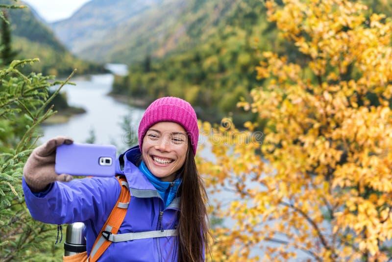 Glückliche asiatische Wandererfrau, die draußen Smartphone selfie am szenischen Standpunkt in der Naturfallberglandschaft nimmt M lizenzfreie stockbilder
