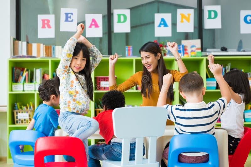 Glückliche asiatische weiblicher Lehrer- und Mischrassekinder im Klassenzimmer, Kindergartenvorschulekonzept lizenzfreies stockfoto