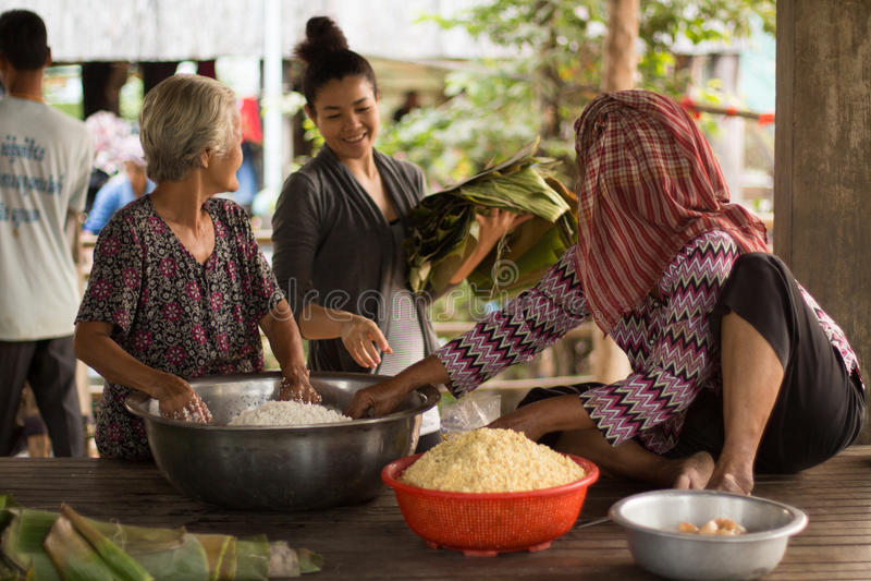 Glückliche Asiats-Kambodscha-Khmer-Frau, die Reis-Kuchen mit Bohnen und Bananen-Blättern macht lizenzfreie stockfotografie