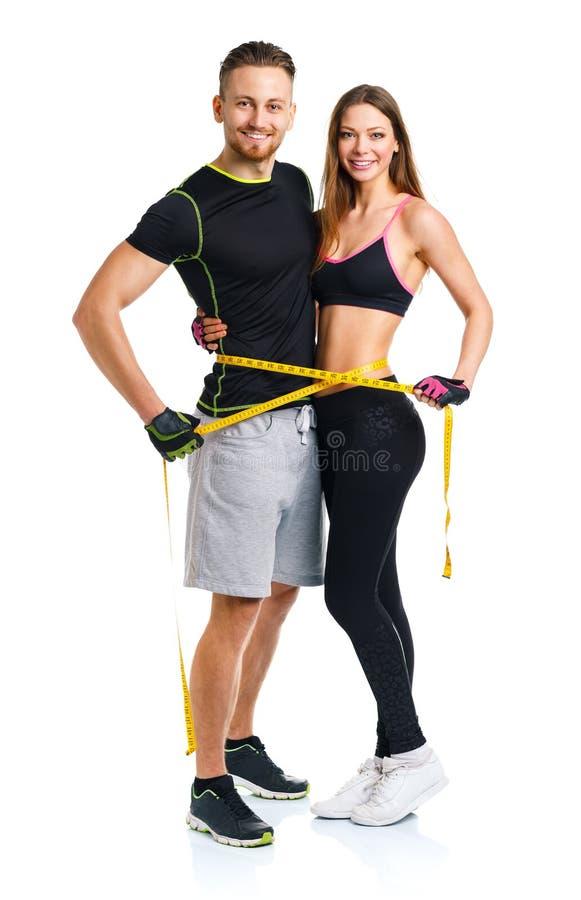 Glückliche athletische Paare - Mann und Frau mit messendem Band stockfotografie