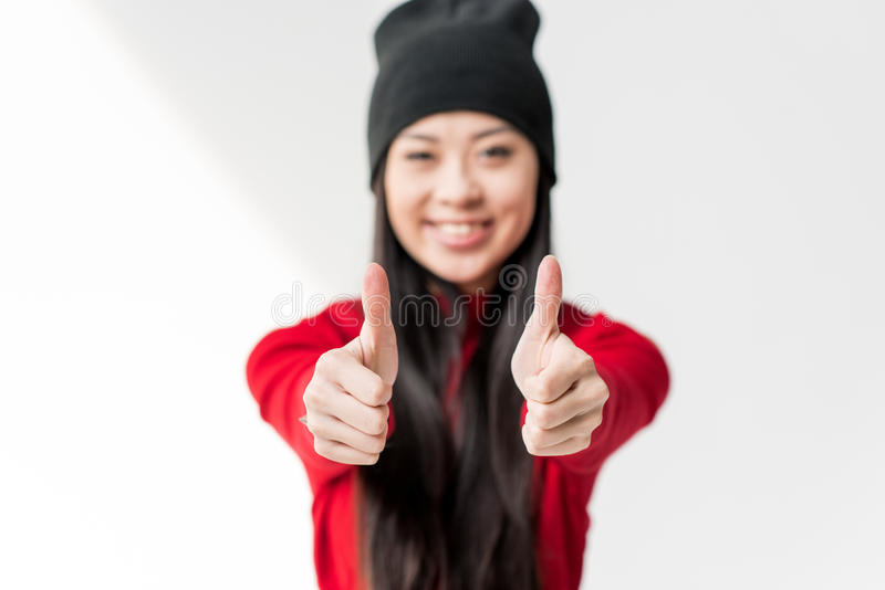 Glückliche attraktive asiatische Frau, die sich Daumen zeigt lizenzfreies stockfoto
