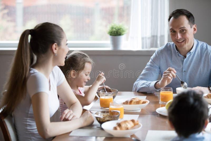 Glückliche attraktive Familie, die gesundes Frühstückssitzen in hat stockfotografie