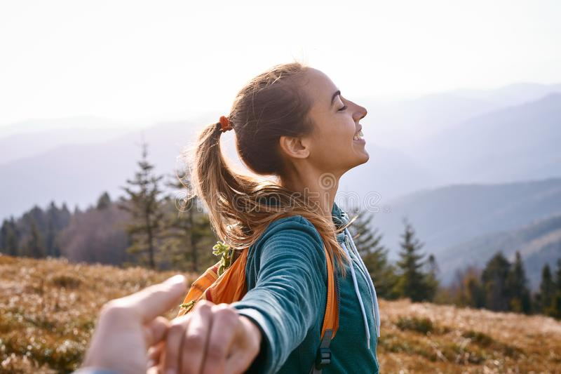 Glückliche attraktive Frauenwandererstellung auf dem Berghang gegen Hintergrund des Sonnenuntergangs stockfoto
