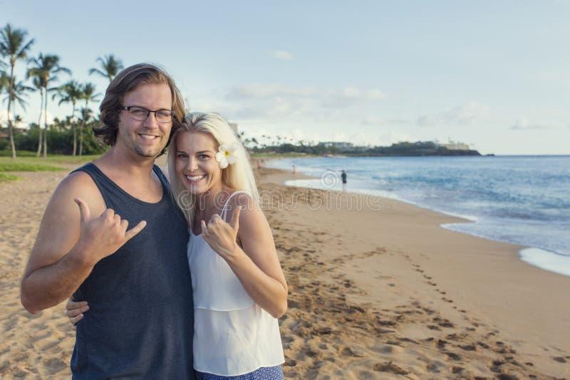 Glückliche attraktive Paare auf hawaiischen Strand-Ferien stockbild