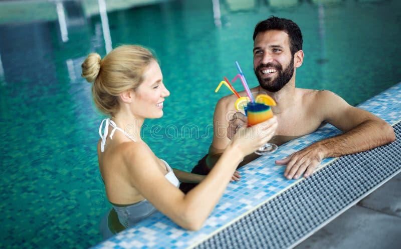 Glückliche attraktive Paare, die im Swimmingpool sich entspannen stockbild