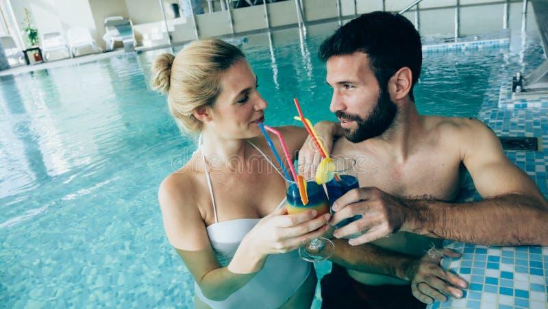Glückliche attraktive Paare, die im Swimmingpool sich entspannen lizenzfreies stockfoto