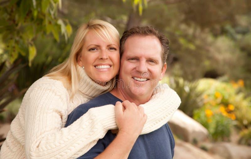 Glückliche attraktive Paare im Park lizenzfreie stockfotos