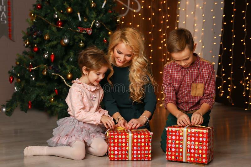 Glückliche aufgeregte Eltern, die wie Tochter öffnet Weihnachten vorhanden schauen lizenzfreie stockfotografie