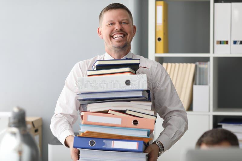 Glückliche Büroangestellte tragen riesige Papierstapel lizenzfreie stockfotos