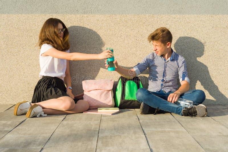 Glückliche Bahn der Studenten auf dem Campus, Jugendliche sitzen auf der grauen Wand, las Lehrbücher, trinken Wasser, betrachten  lizenzfreie stockbilder
