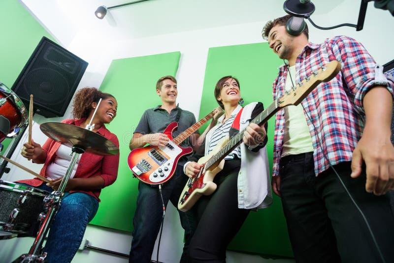 Glückliche Band-Mitglieder, die im Tonstudio durchführen lizenzfreie stockbilder