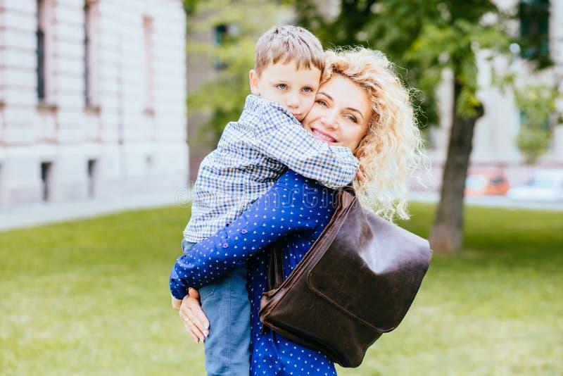 Glückliche blonde gelockte Mutter, die Spaß mit ihrem Kind im Sommerpark im Freien hat Jugendlicher Sohn, der seine Mama im Freie lizenzfreies stockfoto